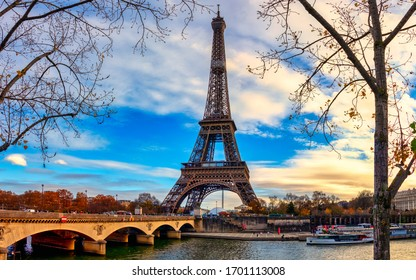 Paris, France - November 25, 2019 - CItyscape of Paris in fall. Ships and brigde over Seine river with Eiffel tower in background and dramatic cloudy sky.