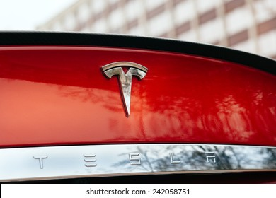 PARIS, FRANCE - NOVEMBER 29, 2014: Tesla Model S signage of a red car at Paris showroom, France. Tesla is an American company that designs, manufactures, and sells electric cars