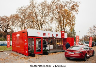 PARIS, FRANCE - NOVEMBER 29, 2014: Customer admiring new Tesla Model S at showroom  in Paris, France. Tesla is an American company that designs, manufactures, and sells electric cars