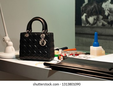 """Paris / France - November 29, 2017: Lady Dior bag, displayed in workshop space alongside production and craft materials in """"Christian Dior, Couturier du Rêve"""" exhibition in Musée des Arts Décoratifs."""