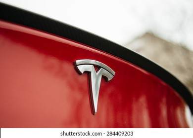 PARIS, FRANCE - NOVEMBER 29: Tesla Motors logo on a red car. Tesla is an American company that designs, manufactures, and sells electric cars