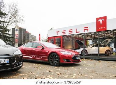 PARIS, FRANCE - NOVEMBER 29: Tesla Model S showroom and two luxury tesla cars outside and one inside. Tesla is an American company that designs, manufactures, and sells electric cars