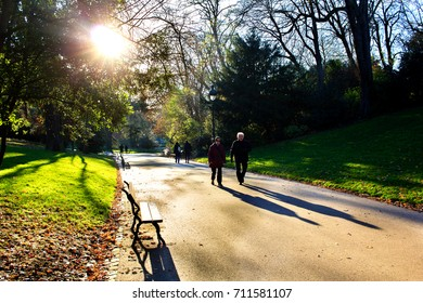PARIS, FRANCE - NOVEMBER 29th, 2016 : people walking in the alleyways of the deep autumn Buttes Chaumont garden in Paris. Autumn sun lays down deep shadows of people and objects.