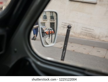 PARIS, FRANCE - NOVEMBER 5, 2018: An antique oldtimer classic car Citroen 2CV seen in the side mirror of another Citroen 2CV