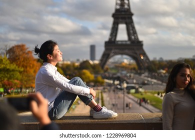 PARIS, FRANCE - NOVEMBRE 9, 2018: Tourists making photos in Trocadero site with Tour Eiffel in the background in an autumn day