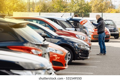 PARIS, FRANCE - OCT 10, 2015: Man choosing new car - looking at the big trunk - new car to choose the most precious one