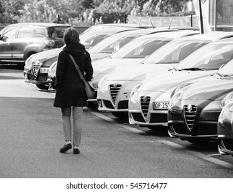 PARIS, FRANCE - OCT 10, 2015: Woman walking between rows of new car to choose the most precious one at the Alfa Romeo car store black and white