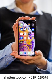 PARIS, FRANCE - OCT 2, 2018: business woman demonstration of the new Apple iPhone Xs Max smartphone telephone from Apple Computers with all home apps on OLED display