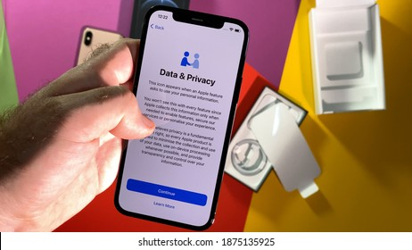 Paris, France - OCt 25, 2020: POV male hand setting new iPhone 12 Pro latest smartphone with 5g reading about data and Privacy during setup