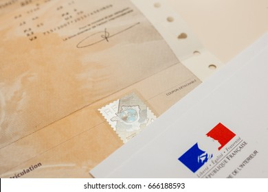 PARIS, FRANCE - OCT 26, 2016: Special postal envelope with the logo of The Ministry of the Interior next to holographic security stamp issued by Minister above the vehicle registration certificate