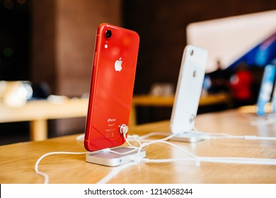 PARIS, FRANCE - OCT 26, 2018: Latest iPhone XR product red smartphone in Apple Store Computers during the launch day with Designed by Apple in California and Assembled in China tag
