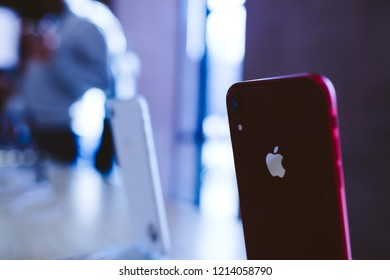 PARIS, FRANCE - OCT 26, 2018: Latest red iPhone XR smartphone in Apple Store Computers during the launch day - magenta color cast