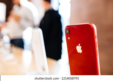 PARIS, FRANCE - OCT 26, 2018: Focus on Apple logo on the latest iPhone XR smartphone in Apple Store Computers during the launch day with customer in background