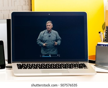 PARIS, FRANCE - OCT 28 2016: Apple Computers website on new MacBook Pro Retina with OLED Touch bar in geek creative room showcasing Apple Keynote - Philip Schiller speaking