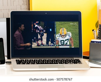 PARIS, FRANCE - OCT 28 2016: Apple Computers website on new MacBook Pro Retina with OLED Touch bar in geek creative room showcasing Apple Keynote presentation of Tv app by Apple Nfl game