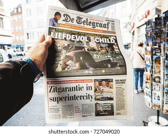 PARIS, FRANCE - OCT 3, 2017: Man buying De Telegraaf newspaper with socking title photo press kiosk about the 2017 Las Vegas Strip shooting in United States with about 60 fatalities and 527 injuries