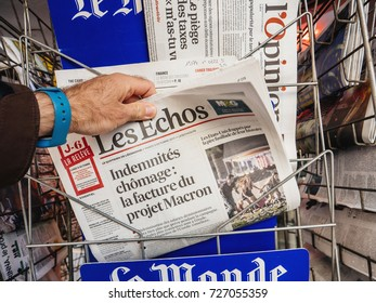 PARIS, FRANCE - OCT 3, 2017: Man buying  newspaper with news from Spain about the Catalonia Referendum and protests