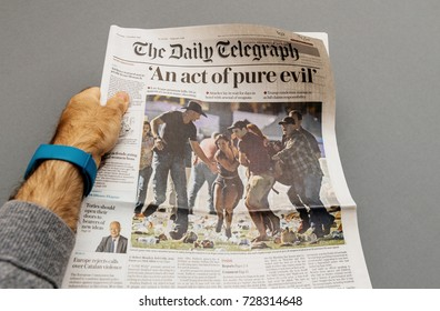 PARIS, FRANCE - OCT 3, 2017: Man holding The Daily Telegraph newspaper cover with socking title Pure Evil and photo after Las Vegas Strip shooting in United States