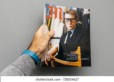 PARIS, FRANCE - OCT 4, 2017: Man holding M Magazine le monde with Yves Saint Laurent fashion icon on the cover