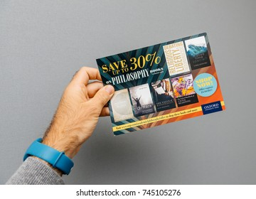 PARIS, FRANCE - OCT 4, 2017: Male hand holding against grey background special offer discount flyer from Oxford University Press for philosophy books