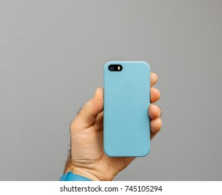 PARIS, FRANCE - OCT 4, 2017, Man holding iPhone 5 SE smartphone against grey background showing the blue leather protection case with Apple Computers logo