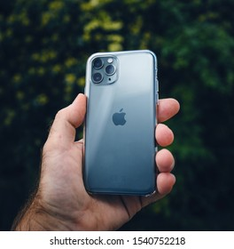 Paris, France - Oct 4, 2019: Square image of man hand holding against green park background the new Apple Computers iPhone 11 Pro with Clear protection case