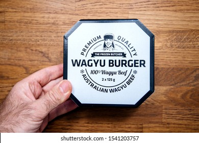 Paris, France - Oct 4, 2019: Young man hand holding above kitchen counter Wagyu Burger with Premium Quality made from Australian Wagyu beef