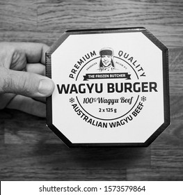 Paris, France - Oct 4, 2019: Above view of man hand holding above kitchen counter Wagyu Burger with Premium Quality made from Australian Wagyu beef - black and white square image