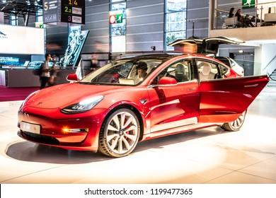 Paris, France, October 02, 2018: metallic red Tesla Model 3 at Mondial Paris Motor Show, produced by American automaker Tesla, main shareholder Elon Musk,