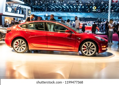 Paris, France, October 02, 2018: metallic red Tesla Model 3 at Mondial Paris Motor Show, produced by American automaker Tesla, main shareholder Elon Musk,