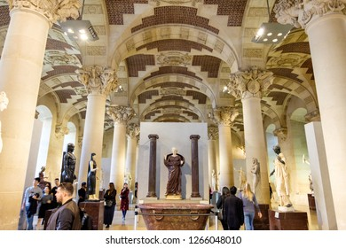PARIS, FRANCE - OCTOBER 03, 2018: Wide angle view inside Louvre. White colums in the background and foreground. People admire the artworks around the room