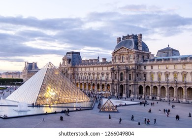 PARIS, FRANCE - OCTOBER 03, 2018: Louvre museum at sunset. Magenta look in the horizont. Tourists walking in the square. Soft clouds in the sky