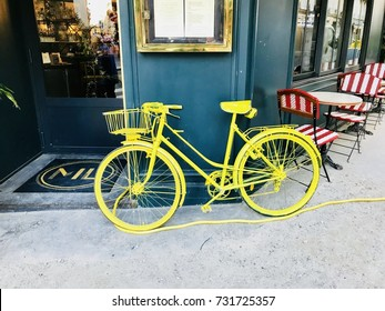 PARIS, FRANCE - OCTOBER 04, 2017 -   old style yellow bicycle in front of the Paris restaurant