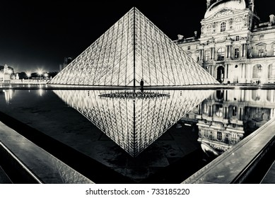 PARIS, FRANCE - OCTOBER 04, 2017 -  suggestive image of the pyramid reflected on the fountain of the Louvre museum in Paris at night