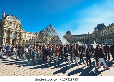 PARIS, FRANCE - OCTOBER 05, 2016: Famous Louvre Museum with Pyramid at sunny autumn day. Louvre is one of the largest and most visited museums worldwide