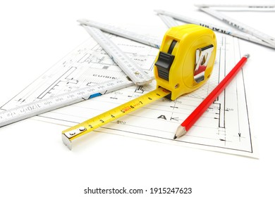 Paris, France -  October 09, 2010: arranged on house construction plans with tape measure, pencil and wooden ruler. Shooting studio photo isolated on white background.