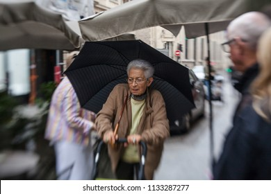 Paris, France - October 1, 2016. middle-aged  woman with umbrella  walking on the streets of  Paris  in rainy weather.  Morning city  life