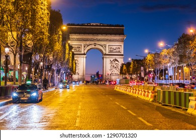 PARIS FRANCE - OCTOBER 1, 2018: Empty road leading to the Arc de Triomphe in Paris, France. Golden lightsources hitting the ground reflects on the entire street. Shot at night