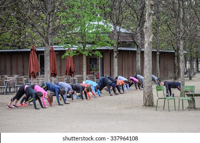 PARIS, FRANCE - October 1: Tuileries Garden in Paris, France on October 1, 2015. A group of people with a trainer doing exercises outdoors