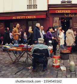 Paris, France - October 11, 2014: backside view of older man selling treats and snacks in crowded street of Montmartre while people walk by.