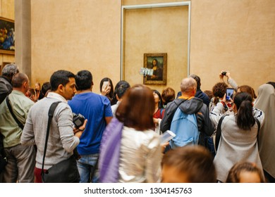 "PARIS, FRANCE - October 11, 2016: Visitors take photo of Leonardo DaVinci's ""Mona Lisa"" at the Louvre Museum"
