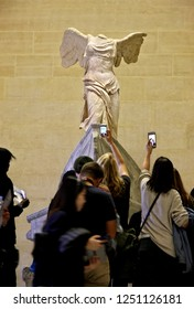 """PARIS, FRANCE- October 13, 2016. Visitors gathered in front of the """"Winged Victory (""""Nike"""") of Samothrace"""", in the Louvre museum, Paris, France"""