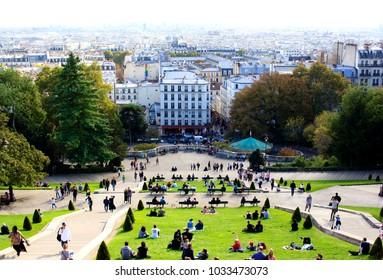 PARIS, FRANCE - OCTOBER 13th, 2017 : View from the Montmartre hill to the green lawn in front of the Sacre Coeur church with tourists relaxing and enjoying sunny weather while looking over Paris.
