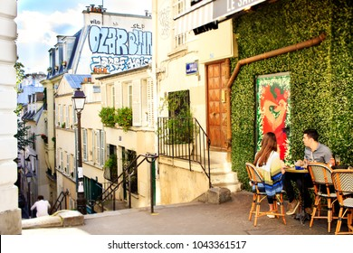 PARIS, FRANCE - OCTOBER 13th, 2017 : young couple having lunch in the traditional cafe at Monmartre area in Paris, France