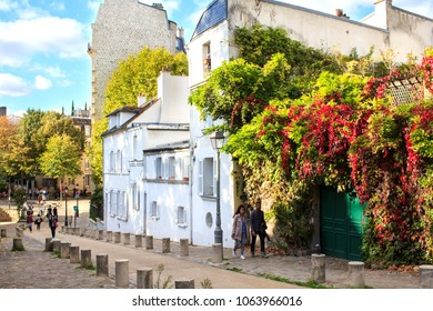 PARIS, FRANCE - OCTOBER 13th, 2017 : Couple walking at one of the picturesque side streets of the famous Montmartre hill in Paris, France. It is set by old typical houses couvered by creeper plants.