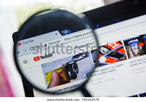 Paris, France - October 19, 2017 : YouTube logo of website france home page magnified with magnifying glass.