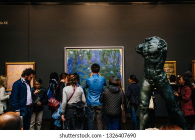 PARIS, FRANCE - October 2, 2016: Visitors in permanent collection hall of Musee d'Orsay. Musee d'Orsay has the largest collection of impressionist and post-impressionist paintings in the world