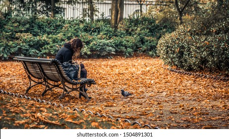 Paris, France - October 2018 : Lonely woman sat on a bench tapping on her smartphone in the Luxembourg Gardens, in Paris France on an Autumn day