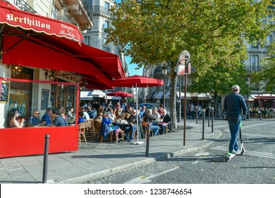 Paris / France - October 21 2018: Street view of the Ile St Louis with the famous bistro ice cream shop Berthillon with people at the outdoor tables