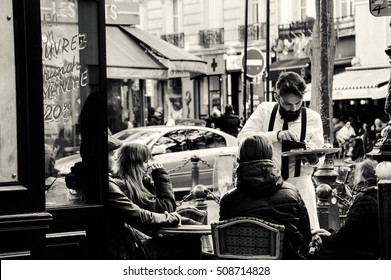 PARIS, FRANCE - OCTOBER 22, 2016: Waiter serving customers at traditional outdoor Parisian cafe on rue Mouffetard which is popular market and nightlife street in Latin Quarter.